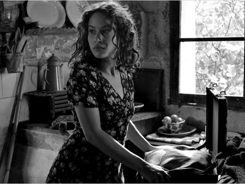 Une jeune femme est debout dans une cuisine, devant une fenêtre, elle regarde derrière elle