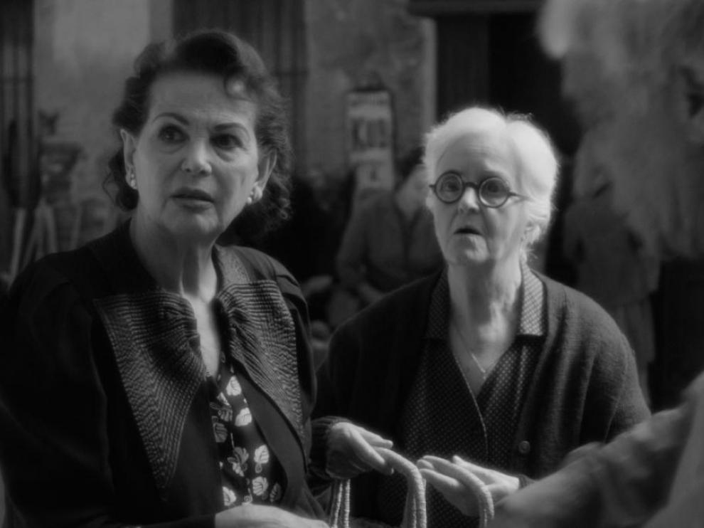 Deux femmes, au centre de l'image, regardent dans la même direction