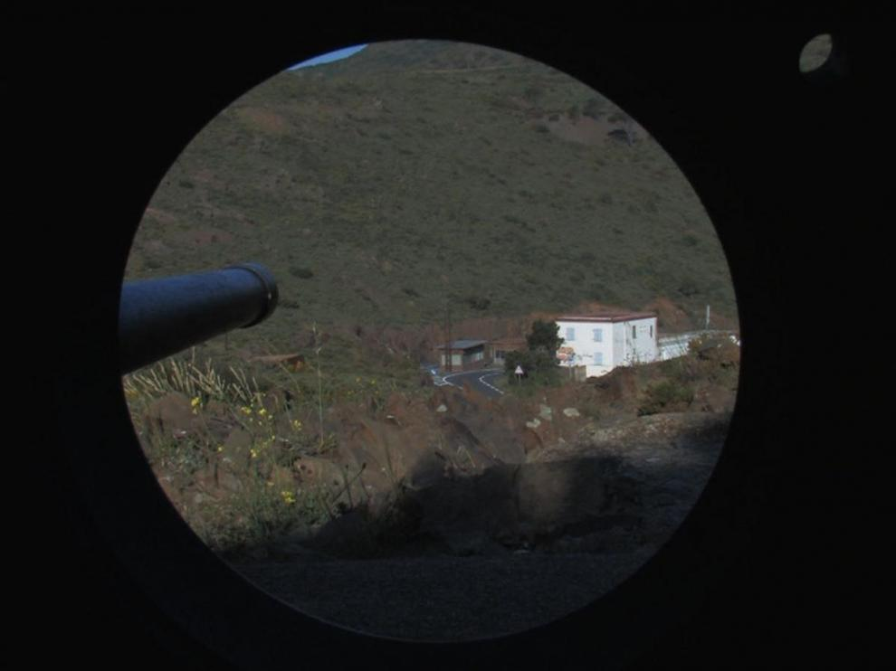 Fish eye : point de vue du viseur d'un fusil, qui pointe une maison au loin