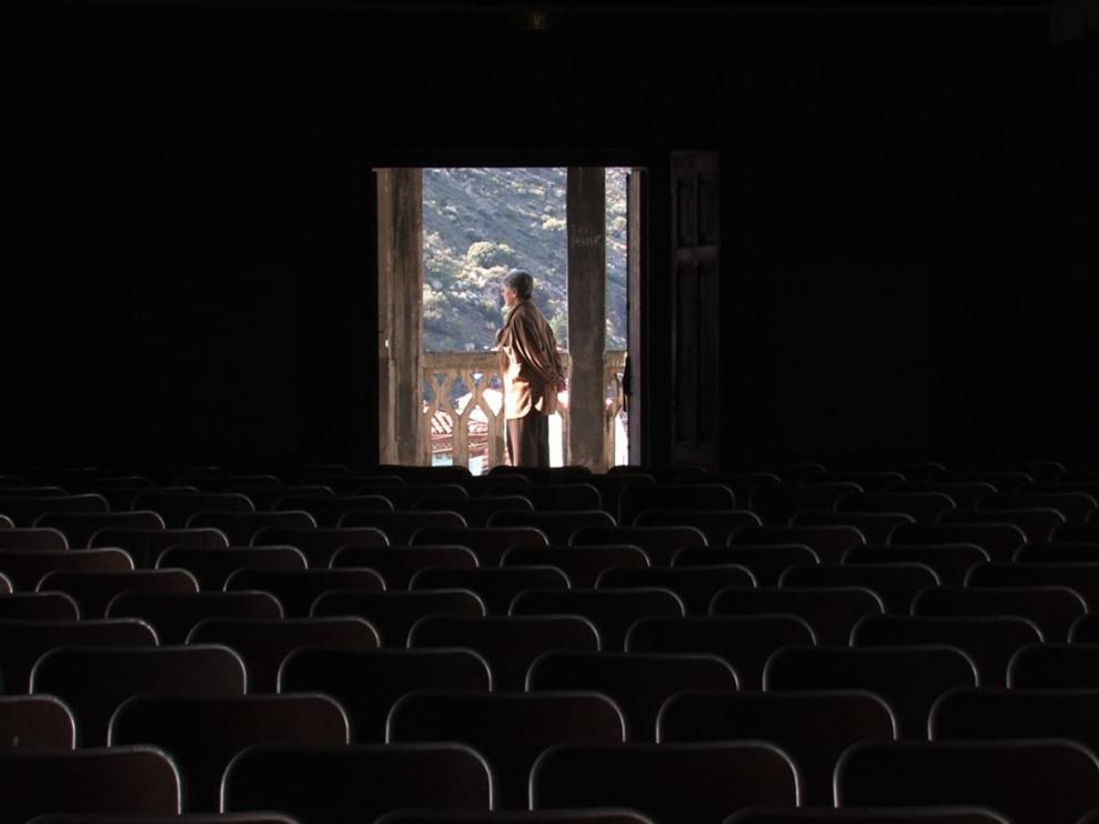 Au fond d'une salle de cinéma plongée dans l'obscurité, une fenêtre est ouverte, dans son entrebâillement, une personne, debout, fait face aux montagnes