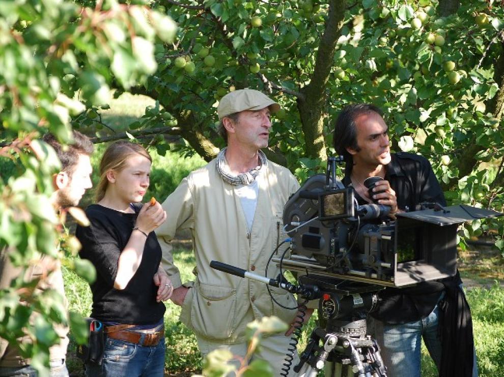 Homme avec une caméra, derrière lui, deux personnes