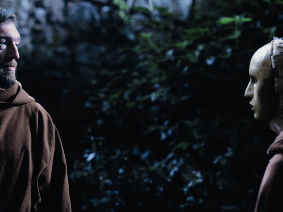 Deux moines parlent, de nuit. L'un d'eux porte un masque qui recouvre l'intégralité de son visage