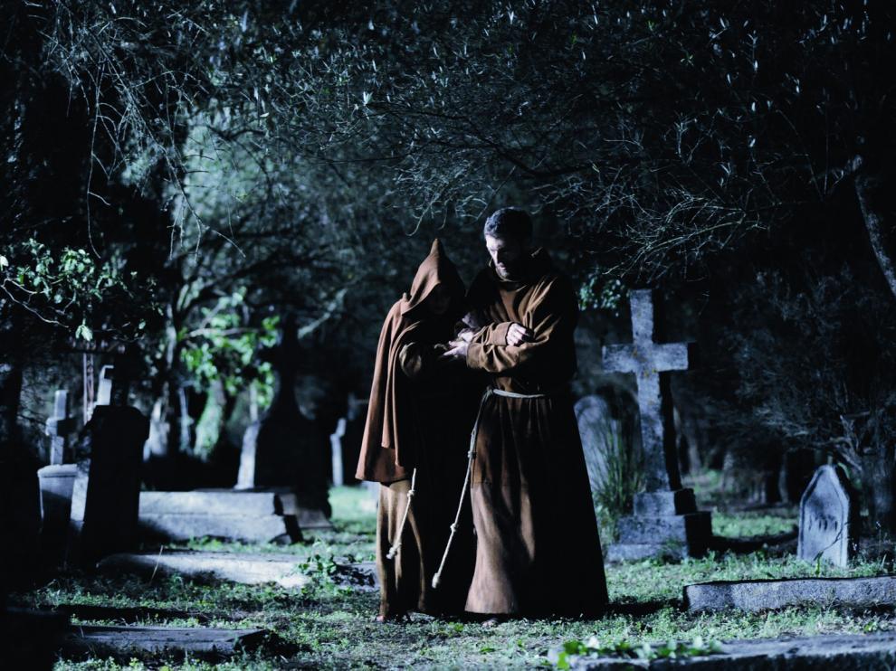 Deux moines marchant de nuit dans un cimetière