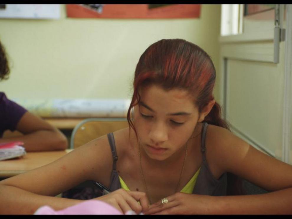 Une jeune fille rom est assise à son bureau, dans une salle de classe, l'air studieux
