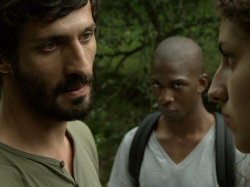 Un homme regarde une jeune femme droit dans les yeux, derrière eux un jeune homme observe la scène, les personnages se trouvent dans la nature