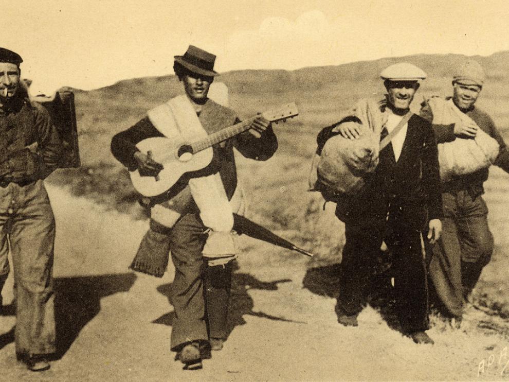 Photo sépia des années 1930, de paysans marchant tout en jouant de la guitare