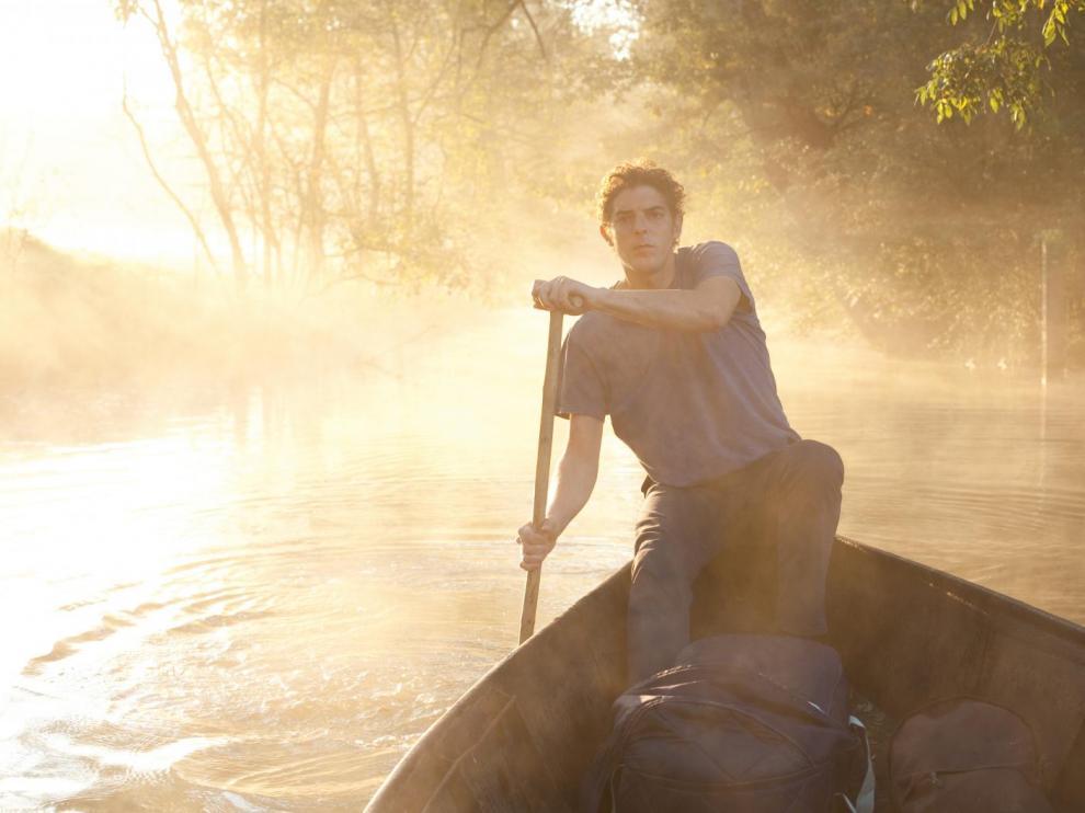 Un homme conduit une barque sur une rivière dans la brume au matin