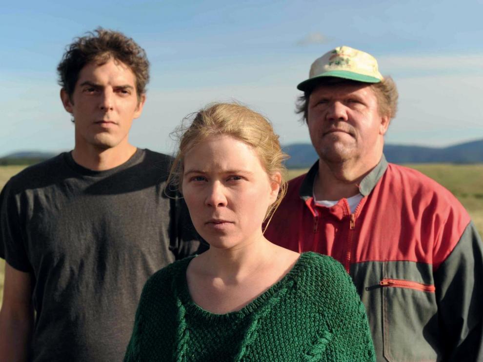 Deux hommes et une femme face caméra, dans un champ