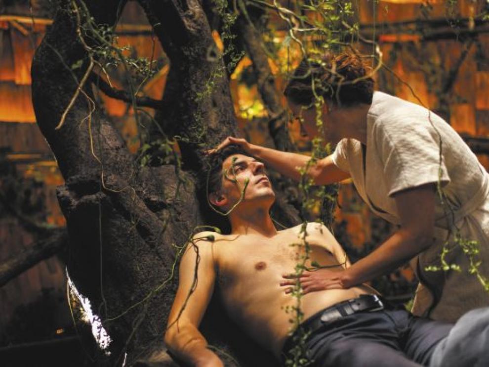 Une femme semble soigner un homme à demi nu dans un décor enchanté