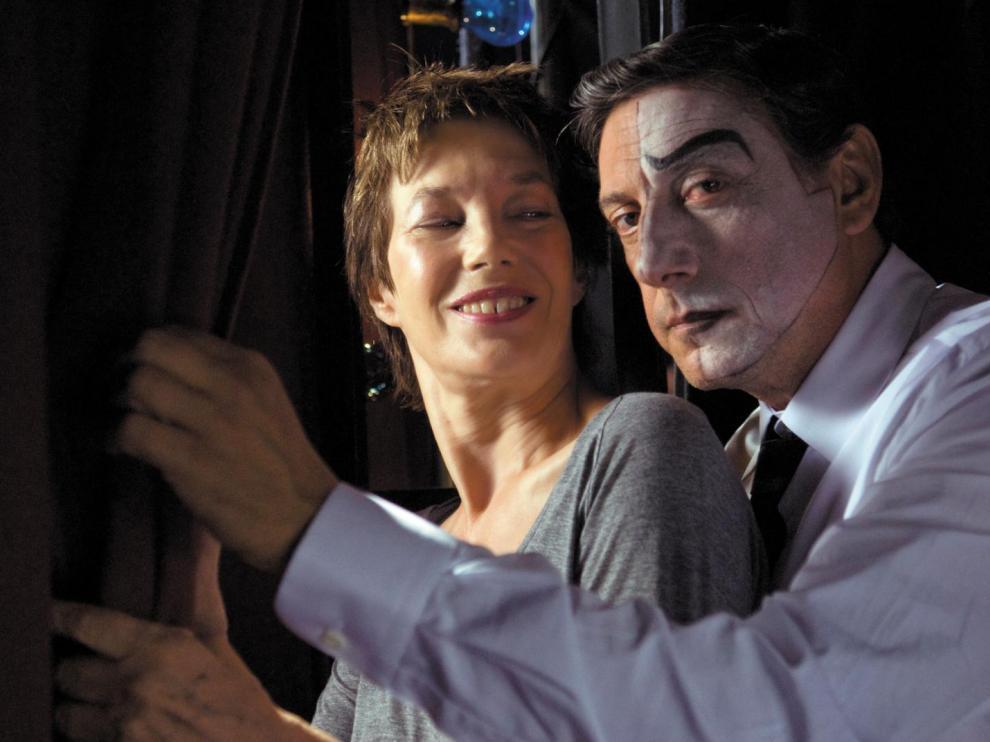 Homme avec un maquillage de clown enlaçant une femme