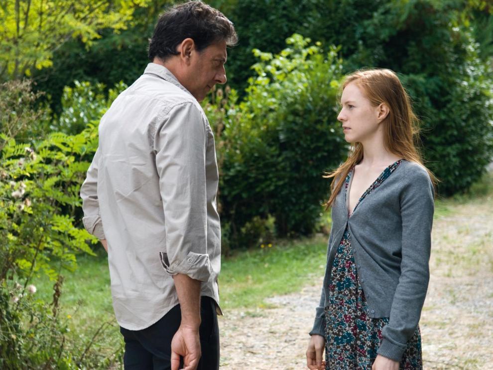 Jeune couple sur un chemin, devant une forêt
