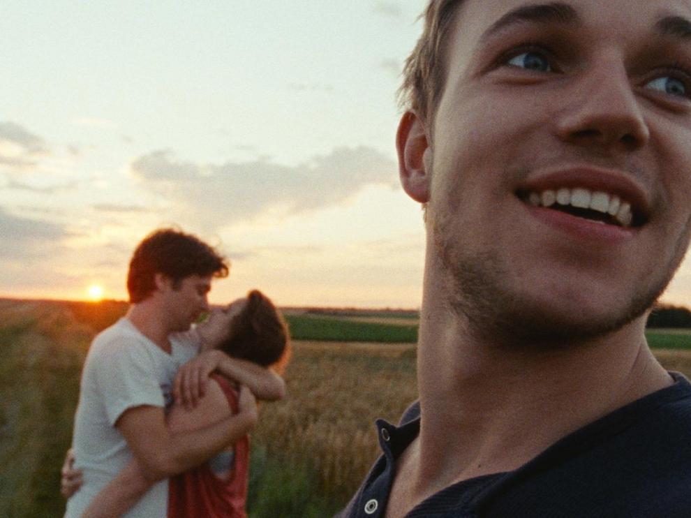 Au premier plan un jeune homme avec un large sourire, derrière lui,