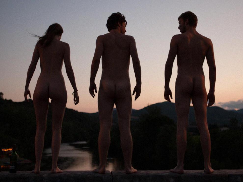 Trois jeunes sont nus devant une étendue d'eau, à côté d'eux, une bouteille de vin