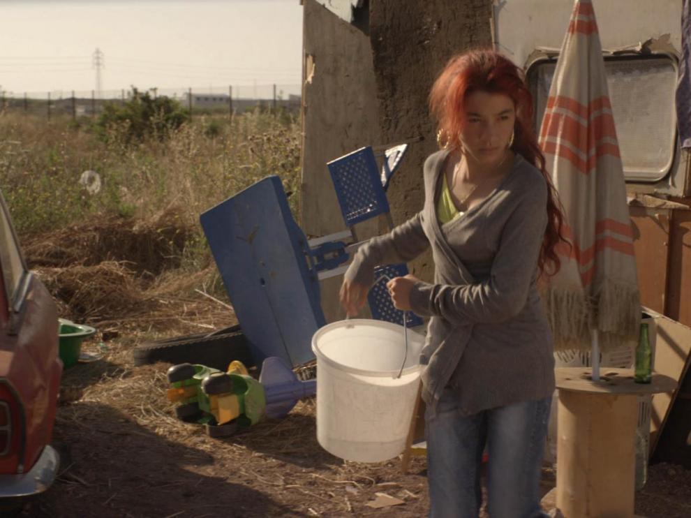 Une jeune fille rom vide un seau d'eau devant un logement de fortune