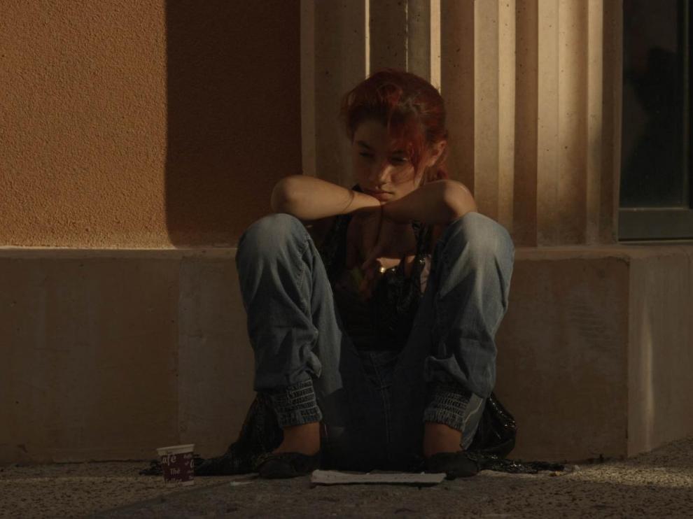 Une jeune fille rom est assise contre un mur, les genoux repliés sur la poitrine, elle regarde au loin