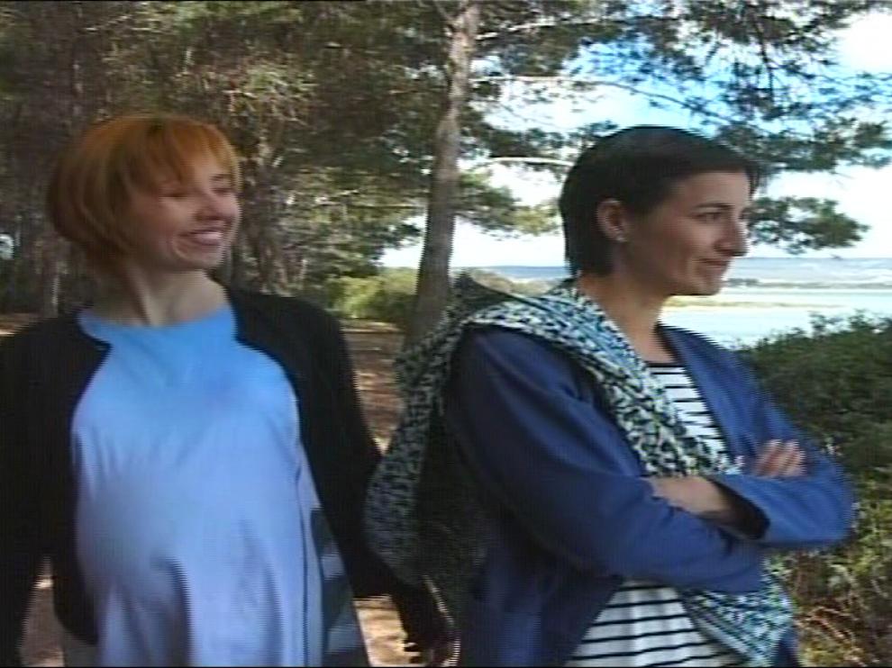 Deux femmes, dont l'une est enceinte, marchent dans une forêt, au bord d'une étendue d'eau