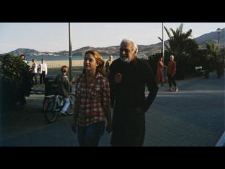 Un homme d'âge mur et une jeune fille marchent sur une promenade