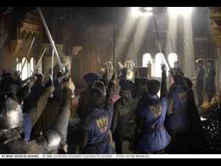 Dans une des salles d'un château, une vingtaine de chevaliers lèvent leurs épées