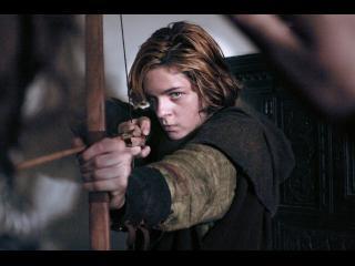 Un jeune homme brun vise un point au loin avec son arc