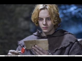 Un jeune homme blond lit une lettre