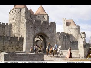Des chevaliers et des gentes dames sortent par l'entrée principale du château comtal de Carcassonne ayant servi de décor au film