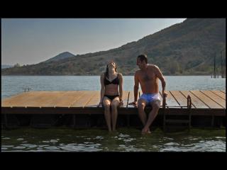 Couple en maillot de bain assis sur un ponton, les pieds dans l'eau