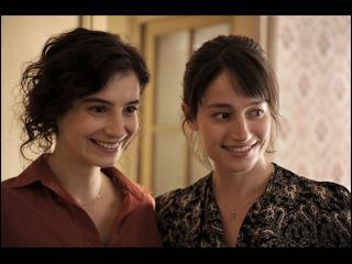 Deux femmes brunes l'une à côté de l'autre, souriantes