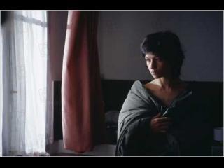 Une femme dans une chambre, enveloppée dans une couette, regarde par la fenêtre d'un air triste