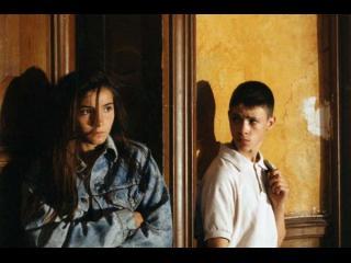 Une jeune fille et un jeune garçon sont adossés à un mur, elle regarde au loin tandisqu'il la regarde