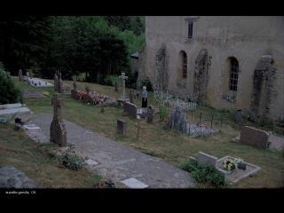 Femme debout devant une tombe, au cimetière