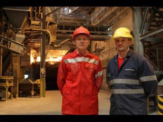 Deux ouvriers en tenue de travail sont debout, dans une usine