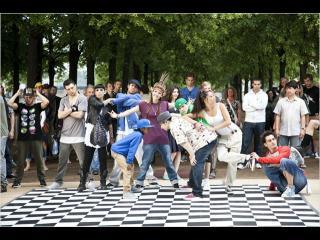 Sur un damier d'échecs grandeur nature, des danseurs font une chorégraphie, devant des spectateurs