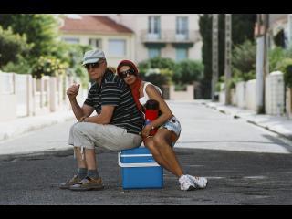 Un couple assis sur une glacière bleue, au milieu de la route