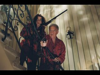 Un couple dans un escalier, l'homme pointe un revolver sur quelqu'un hors cadre