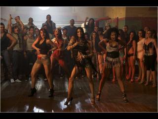 Dans une salle, un groupe de danseuses fait une démonstration au reste de l'assemblée
