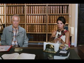 Un couple assis dans un bureau dont les murs sont recouverts de livres