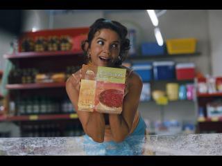 """Une femme montre une boîte en carton sur laquelle est inscrit et illustré """"Tiramisu glacé"""""""