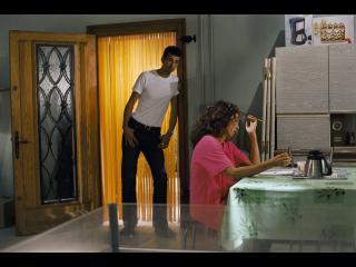 Une femme est assise à une table et lit un cahier ; derrière elle, dans l'ouverture  de la porte, un homme la regarde