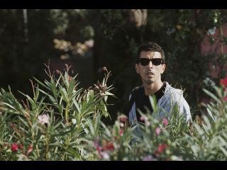 Homme observant quelque chose au loin, derrière des lauriers roses