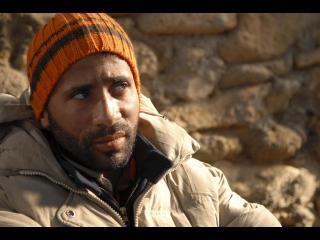 Gros plan sur le visage d'un homme adossé contre un mur de pierre