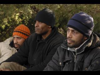 Trois hommes portant des bonnets, assis les uns à côté des autres