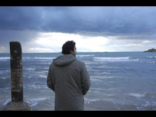 Homme debout devant la mer de prés