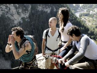 Quatre randonneurs sont sur le bord d'une falaise, l'un d'eux crie quelque chose en direction du vide