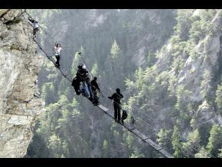 Photo de tournage : l'équipe technique et les acteurs principaux sont sur un pont fait de câbles et de planches, suspendus entre deux versants d'une montagne