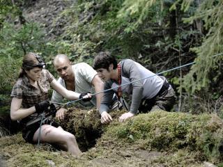 Trois randonneurs au sol, l'une d'entre eux s'apprête à descendre en spéléo dans un trou