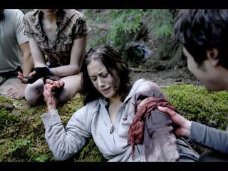 Une jeune fille avec un garrot ensanglanté autour du bras est allongée au sol, trois personnes sont autour d'elle