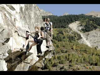 Cinq randonneurs escaladent le versant d'une montagne pour en faire le tour