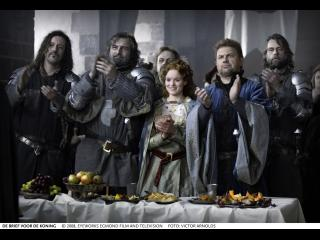 Une femme et cinq chevaliers, derrière une table couverte de mets, applaudissent en réaction à quelque chose en face d'eux