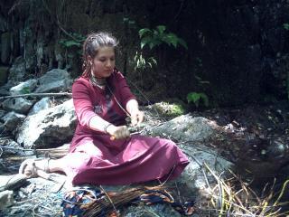 Une jeune fille est assise sur une pierre, en tailleur, elle a les bras tendus devant elle