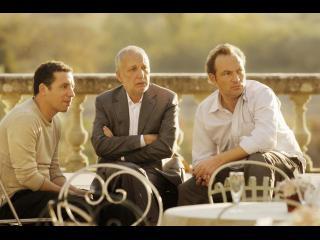 Trois hommes, assis devant une rembarde en pierre, regardent au loin